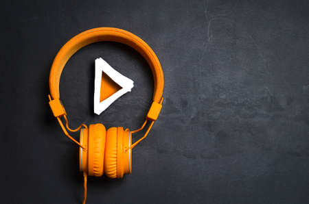 Photo pour Play button and orange headphones on dark concrete background - image libre de droit