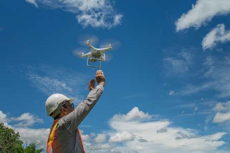 Foto de Young engineer use drones outdoor with beautiful sky with clouds, the man holding Drone - Imagen libre de derechos