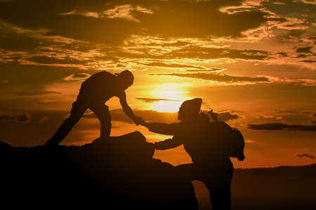 Foto de Two friends helping each other and with teamwork trying to reach the top of the mountains during wonderful summer sunset. - Imagen libre de derechos