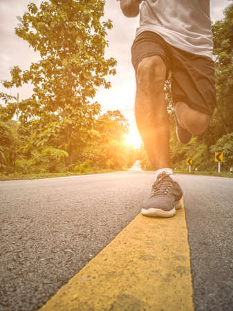 Photo pour Young male running on a rural road during sunset. - image libre de droit