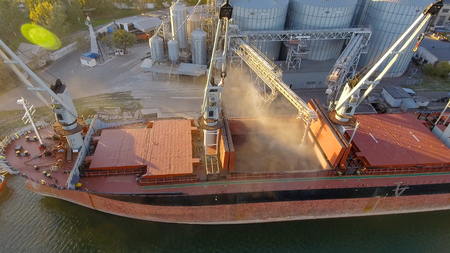 Foto de Aerial view of big grain elevators on the sea. Loading of grain on a ship. Port. Cargo ship - Imagen libre de derechos