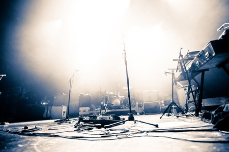 Photo for Empty illuminated stage with drumkit, guitar and microphones - Royalty Free Image