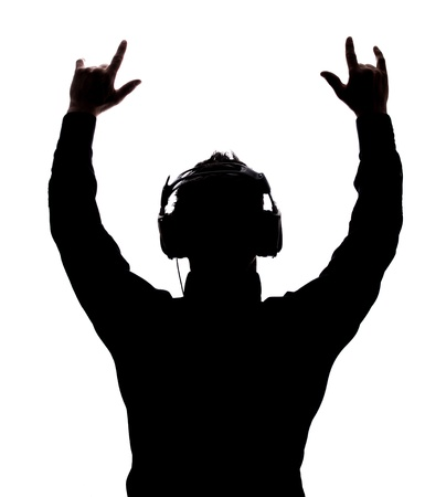 Photo for Man rocking on with headphones in silhouette isolated over white background - Royalty Free Image