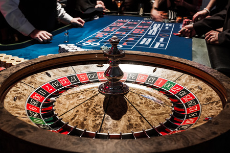 Foto de Wooden Shiny Roulette Details in a Casino with Blurry People and Croupier in Background - Imagen libre de derechos