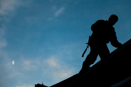 Photo pour Contractor in Silhouette working on a Roof Top with blue Sky in Background - image libre de droit