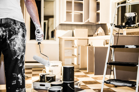 Photo pour Mess of All kind of Painting Equipment in the Kitchen and Discouraged Man - image libre de droit