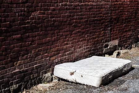 Foto de Old and dirty Abandoned Mattress in a Backstreet - Imagen libre de derechos