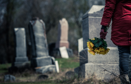 Photo for Close-up of a Sad Woman Holding Sunflowers in front of a Loved one's Gravestone. Focus on the Bouquet. - Royalty Free Image