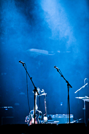Photo for Lighted Empty Stage and Fog with Microphones and Guitar - Royalty Free Image