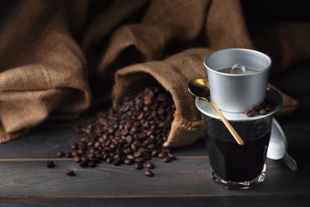 Foto de Vintage vietnam coffee dripper, coffee cup and coffee beans with bag. dark food style - Imagen libre de derechos