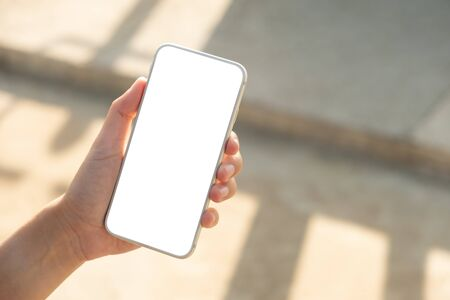 Foto de Woman hand holding and using smart phone with blank screen in the park - Imagen libre de derechos