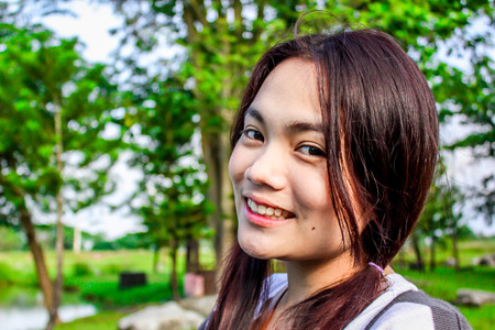 young beautiful asian girl romantic teenage model enjoy relex on the green grass meadow field in sun light, smile thailand siam