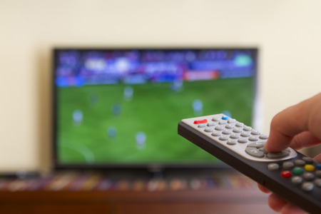 Foto de Watching a soccer match in the television, with a tv remote control in the hand - Imagen libre de derechos