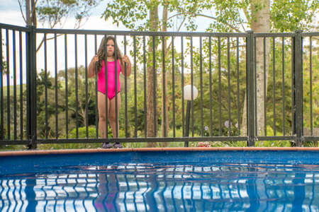 Foto de Pool Safety - Young Girl Standing Outside Pool Fence Looking In To Pool Northland New Zealand - Imagen libre de derechos