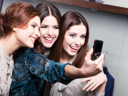 Photo for Three friends photo session on the phone after shopping - Royalty Free Image