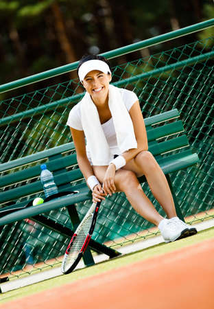 Young female tennis player rests with bottle of water on the bench at the tennis court