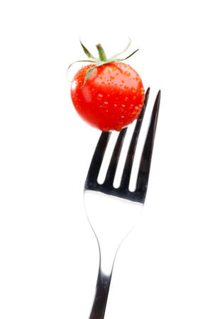 Close up of red tomato on the fork, isolated on white. Healthy dieting food