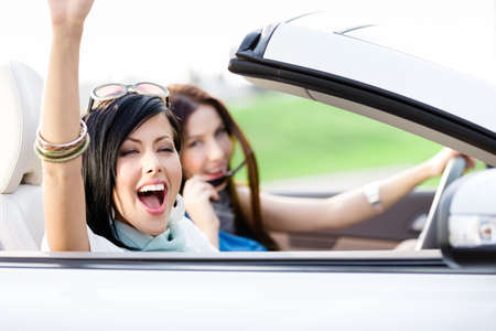 Photo pour Two happy friends in the white car driving everywhere and looking for freedom and fun - image libre de droit