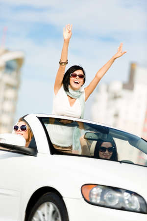 Lovely teenager with her hands up in the car with friends. Girls ride somewhere on vacation