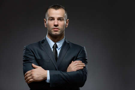 Photo for Half-length portrait of man wearing business suit and black tie with arms crossed - Royalty Free Image