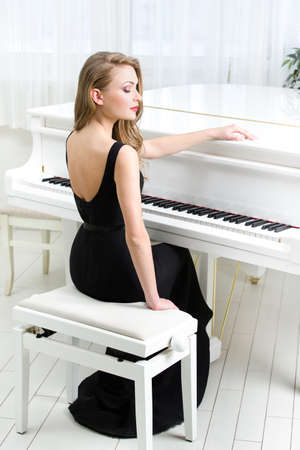 Portrait of woman in black dress sitting and playing piano. Concept of music and arts