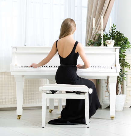 Back view of woman in black dress sitting and playing piano. Concept of music and arts