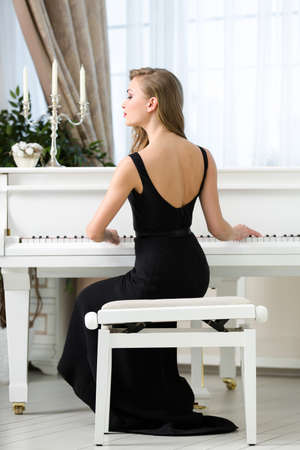 Back view of woman in black dress sitting and playing piano. Concept of music and entertainment