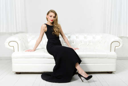 Photo for Woman sitting on white leather sofa. Concept of beauty and perfection - Royalty Free Image