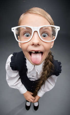 Wide angle portrait of little girl in glasses tongue gesturing, on grey background. Concept of leadership and success
