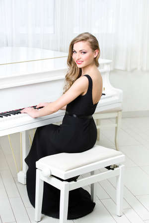 Portrait of woman in black dress sitting and playing piano. Concept of music and art