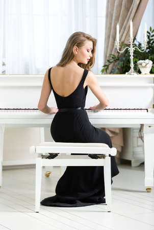 Back view of woman in black dress sitting and playing piano. Concept of music and leisure