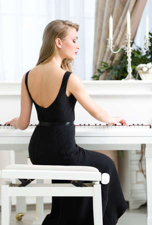 Back view of woman in black dress sitting and playing piano. Concept of music and enjoyment