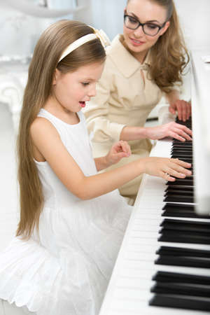 Tutor teaches little girl to play piano. Concept of music study and enjoyment