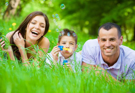 Foto de Happy family of three lying on grass while son blows bubbles. Concept of happy family relations and carefree leisure time - Imagen libre de derechos