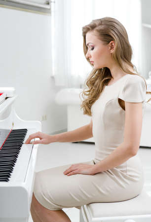 Profile of woman wearing beige dress and playing piano. Concept of music and art