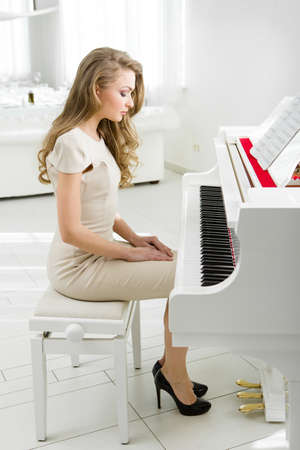 Profile of woman sitting on bench and looking at piano. Concept of music and art
