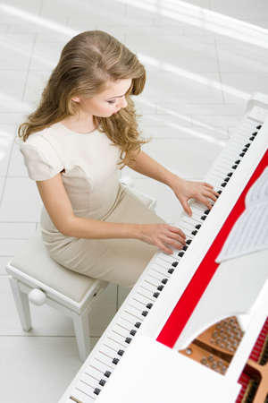 Top view of woman wearing beige dress and playing piano. Concept of music and art