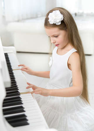 Portrait of little girl in white dress playing piano. Concept of music study and art