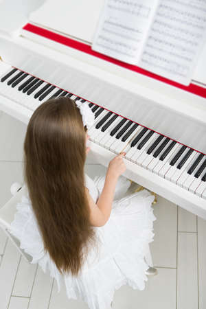 Top view of little girl in white dress playing piano. Concept of music study and arts