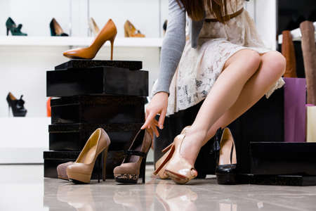 Photo pour Female legs and variety of shoes in the footwear shop - image libre de droit