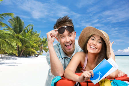Photo pour Couple packs up suitcase with clothing for honeymoon trip, tropical beach background. Concept of romantic vacations and lovely honeymoon - image libre de droit