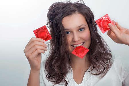 Foto de Smiling girl with  with three red condom packs - Imagen libre de derechos