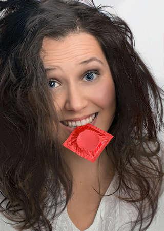 Foto de Smiling girl with  with  red condom pack - Imagen libre de derechos
