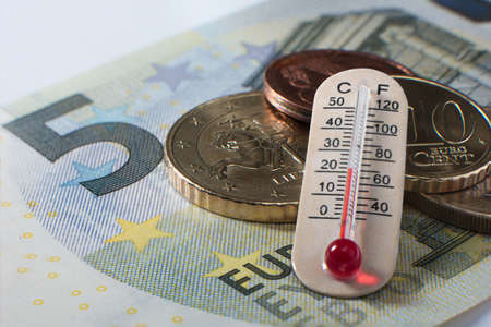 Five euro banknote with some coins and a thermometer showing celsium and fahrenheit temperature