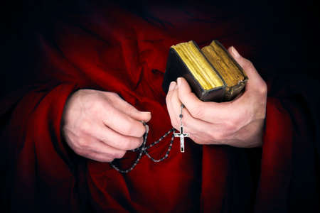 Foto de Mystery monk with a cape holding bibles and a black rosary in his hands - Imagen libre de derechos