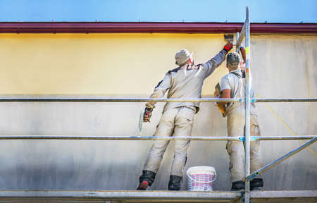 Photo pour Two builders on safety scaffolding  make yellow decorative plaster on the new house wall. Construction - image libre de droit