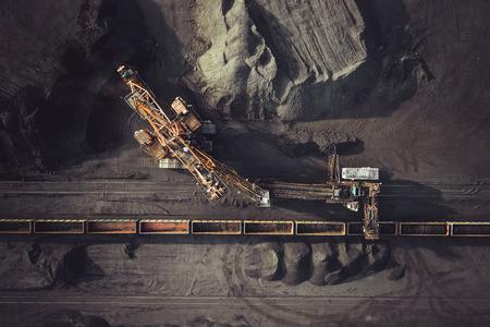 Foto de Coal mining. Aerial view. Excavator loading train cargos - Imagen libre de derechos