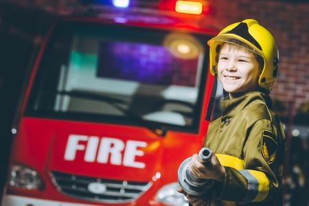 Foto de A boy wearing a firefighter uniform smiling - Imagen libre de derechos