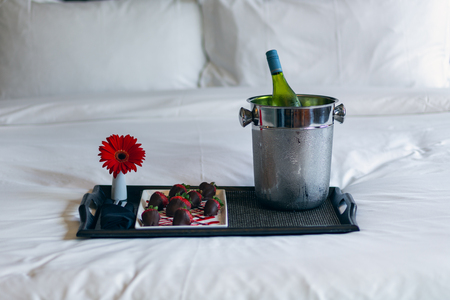 Foto de Chocolate covered strawberries on tray with wine and flower sitting on a bed - Imagen libre de derechos