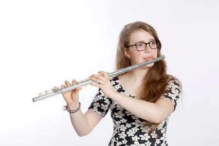 Photo for teenage girl plays the flute against white background - Royalty Free Image
